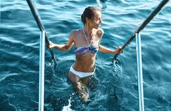 Sexy bikini smiling woman coming out of water holding onto the handrails. Young model with slim weight loss body. Swimming in summer vacation travel royalty free stock photos