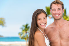 Bikini sun tan couple on beach vacation. Good looking interracial models tanning on tropical holiday background. Asian woman, handsome men relaxing. Skincare royalty free stock images