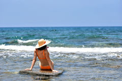 bikini tanning woman relaxing on the beach with a hat Stock Images