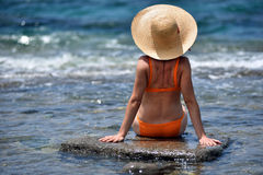 bikini tanning woman relaxing on the beach with a hat Stock Photos