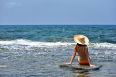 bikini tanning woman relaxing on the beach with a hat Royalty Free Stock Images