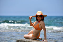 bikini tanning woman relaxing on the beach with a hat Stock Photo