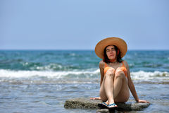 bikini tanning woman relaxing on the beach with a hat Stock Image