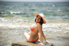 Sexy bikini tanning woman relaxing on the beach with a hat Royalty Free Stock Photo