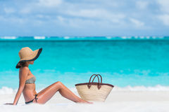 Sexy bikini woman sun tanning - beach bag and hat Royalty Free Stock Images