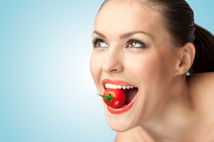 Sexy bite. A creative portrait of a beautiful girl holding a cherry tomato sexually in her teeth Stock Photo