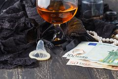 Sexy black lingerie, alcohol and a condom on wooden background. Concept sex for money Royalty Free Stock Image