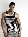 Black man in stripes. Portrait of a fit young male fashion model against white background stock image