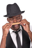 Sexy black man wearing a hat and smelling a cigar Royalty Free Stock Photography