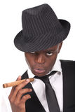 Sexy black man wearing a hat and smoking a cigar Stock Photos
