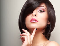 Sexy black short hair style female model looking with finger near the face. Beautiful bright makeup Stock Photography