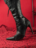Black stiletto heel boot. Black high stiletto heel boot on red stock photo