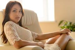 Sexy Blick. Sexy junge Frau, die am Stuhl sitzt und betrachtet Stockbild