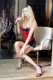 Blond. Woman sitting in the armchair with a glass of liquor royalty free stock images