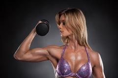 Sexy blond bodybuilder girl with dumbbells. Royalty Free Stock Photography