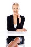 Sexy blond business woman sitting in front of desk Royalty Free Stock Photography