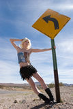 Sexy blond fashion girl by road sign Royalty Free Stock Image