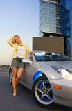 Sexy blond girl. Stands near modern sport car Stock Photo