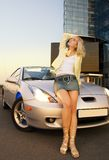 Sexy blond girl. Sits on modern sport car Stock Photography