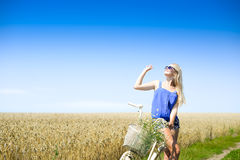 Sexy blond girl on bike with basket looking in sky Royalty Free Stock Photos