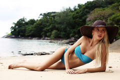 Sexy blond girl in bikini and elegant hat relaxing on tropical beach Royalty Free Stock Photography