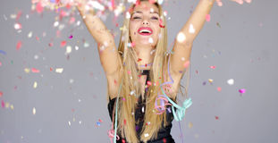 Sexy, blond girl blowing confetti to camera direction Royalty Free Stock Photos