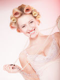 Sexy blond girl with curlers in underwear and beads having fun Stock Images