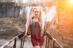 A girl with dreadlocks in a leather jacket and a short skirt stands against the background of an old stone wall in the rays of a b. Sexy blond girl with Royalty Free Stock Photo