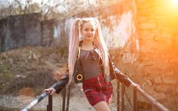 A girl with dreadlocks in a leather jacket and a short skirt stands against the background of an old stone wall in the rays of a b. Sexy blond girl with Stock Images
