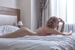 Sexy blond girl lay in huge bed at morning Stock Photo