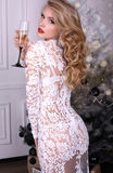 Sexy blond girl in luxurious dress celebrating Christmas Stock Photo