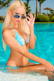 Sexy Blond Girl Sitting in Swimming Pool Stock Image