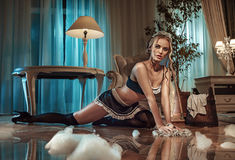 Sexy blond maid cleaning floor in the stylish interior Royalty Free Stock Image