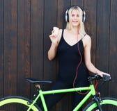 Sexy blond meisje in zwarte bindende uitrusting en tennisschoenen die tegen een houten achtergrond naast een heldere vaste fiets  Royalty-vrije Stock Fotografie
