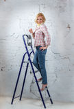 Sexy blond model with lit lantern standing on stepladder Royalty Free Stock Image