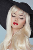 Sexy blond with red lips and long hair wearing in black hat isol Royalty Free Stock Image