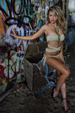 Sexy blond swimsuit model wearing bikini and jewelry posing pretty in front of graffiti background Royalty Free Stock Images