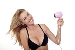 Sexy blond woman. A very sexy blond woman wearing a black bra on a white background using a hair dryer Royalty Free Stock Photos