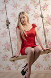 Sexy blond woman. Attractive sexy blond woman in a glamorous red dress sitting on a swing Stock Photography