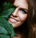 Sexy blond woman behind leaf. Sexy blond woman behind big green leaf Royalty Free Stock Photography