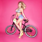 Sexy blond woman with a bicycle. Sexy leggy shapely blond woman in trendy denim shorts and high heels posing with a bicycle on a pink studio background Royalty Free Stock Photo