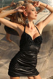 Sexy blond woman in black dress posing beside metallic wall Stock Photo