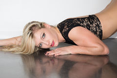 Sexy blond  woman in a black lingerie lying on floor Royalty Free Stock Images