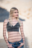Sexy blond woman with flat stomach, shadows lines on her body. Sexy blond woman with perfect flat stomach wear a crop top and jean , shadow lines on her body Royalty Free Stock Photo