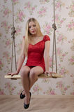 Sexy blond woman. In a glamorous red dress sitting on a swing Stock Images