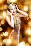 Blond woman on golden background. Blond woman with headphones on golden background stock images
