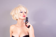 Sexy blond woman holding pistol gun Royalty Free Stock Images