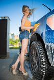 Sexy blond woman. In jeans shorts washing the car outdoors Stock Photos