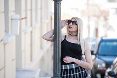 Sexy blond woman leaning on lighting column Royalty Free Stock Image