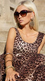 Sexy blond woman  in leopard dress with sunglasses. Sexy blond woman with sunglasses in leopard dress sitting on the stairs at park Royalty Free Stock Images